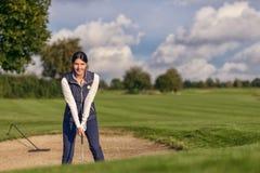 Giocatore di golf della giovane donna in un bunker della sabbia Fotografia Stock