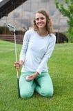 Giocatore di golf della ragazza che colloca sul tee fuori con il driver Immagine Stock Libera da Diritti