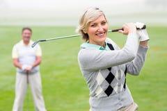 Giocatore di golf di signora che colloca sul tee fuori per il giorno guardato dal partner Fotografia Stock