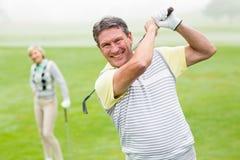 Giocatore di golf felice che colloca sul tee fuori con il partner dietro lui Fotografia Stock Libera da Diritti