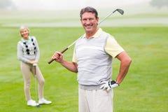 Giocatore di golf felice che colloca sul tee fuori con il partner dietro lui Fotografia Stock