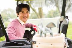 Giocatore di golf felice che conduce il suo carrozzino di golf che sorride alla macchina fotografica Immagini Stock