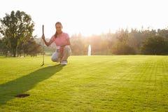 Giocatore di golf femminile che allinea tiro in buca su verde Immagini Stock