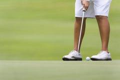 Giocatore di golf femminile che mette sul verde Immagine Stock