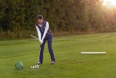 Giocatore di golf femminile che pratica su una gamma di azionamento Immagine Stock