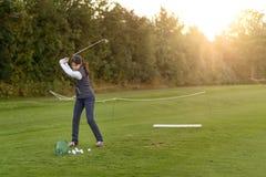 Giocatore di golf femminile che pratica su una gamma di azionamento Fotografie Stock Libere da Diritti
