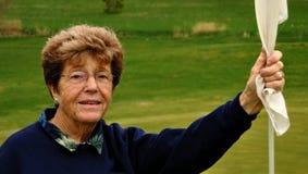 Giocatore di golf maggiore della donna che tiene un Flagstick Fotografia Stock Libera da Diritti
