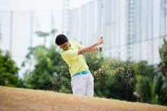 Giocatore di golf maschio che colpisce palla da golf da un separatore di sabbia fotografie stock libere da diritti