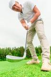 Giocatore di golf maschio concentrato con un club di golf immagini stock