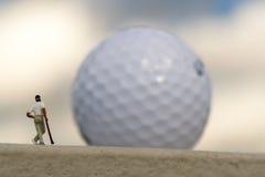 Giocatore di golf miniatura e Golfball vago gigante fotografia stock libera da diritti