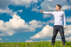 Giocatore di golf nel campo con un bastone per il gioco del golf a destra, Immagine Stock Libera da Diritti