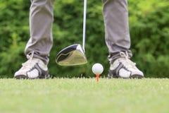Giocatore di golf pronto a collocare sul tee fuori Immagine Stock