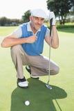 Giocatore di golf sorridente che si inginocchia sul verde mettente Fotografie Stock