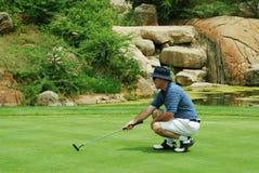 Giocatore di golf sul verde. Fotografie Stock