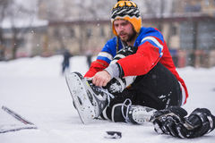 Giocatore di hockey che si siede sul ghiaccio per legare i laccetti Immagini Stock