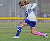 Giocatore di lacrosse della ragazza che è in corsa per la palla immagine stock libera da diritti