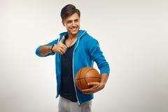 Giocatore di pallacanestro con la palla contro fondo bianco immagine stock