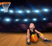 Giocatore di pallacanestro del ragazzo con una palla che si siede sul pavimento nella palestra e sui sogni delle grandi vittorie immagine stock libera da diritti