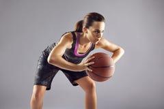 Giocatore di pallacanestro della giovane donna su fondo grigio Fotografie Stock