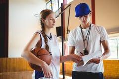 Giocatore di pallacanestro femminile che discute con l'allenatore maschio Fotografie Stock
