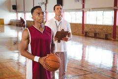 Giocatore di pallacanestro premuroso con l'allenatore Fotografie Stock Libere da Diritti