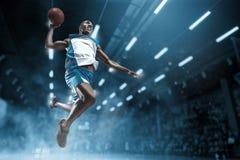 Giocatore di pallacanestro sulla grande arena professionale durante il gioco Giocatore di pallacanestro che fa schiacciata fotografie stock