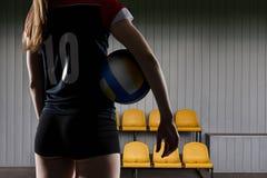 Giocatore di pallavolo femminile che sta con la palla Immagini Stock