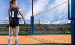 Giocatore di pallavolo femminile che sta con la palla Fotografia Stock Libera da Diritti