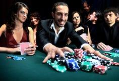 Giocatore di poker che va tutti nella spinta dei suoi chip Immagine Stock