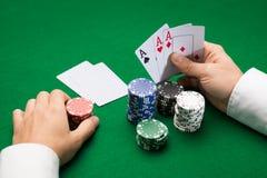 Giocatore di poker con le carte ed i chip al casinò Fotografie Stock