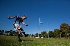 Giocatore di rugby che dà dei calci alla palla per lo scopo contro il chiaro cielo blu Immagini Stock Libere da Diritti