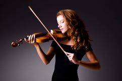 Giocatore musicale femminile contro fondo scuro Immagini Stock
