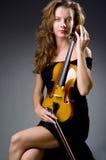 Giocatore musicale femminile contro fondo scuro Immagini Stock Libere da Diritti