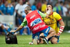 Giocatore non identificato di rugby che riceve la cura da medico del gruppo Fotografia Stock