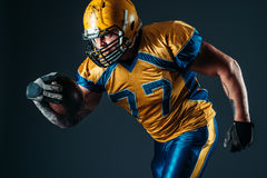 Giocatore offensivo di football americano con la palla Immagini Stock