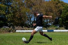 Giocatore risoluto di rugby che dà dei calci alla palla sul campo erboso Immagine Stock Libera da Diritti