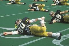Giocatori di football americano che si scaldano con gli allungamenti sul campo prima del gioco, Michie Stadium, NY Immagini Stock