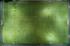 Giocatori di football americano che vanno in giro il campo di football americano Fotografie Stock Libere da Diritti