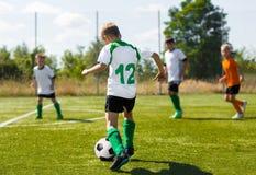 Giocatori di football americano di calcio che corrono con la palla Calciatori che danno dei calci alla palla di calcio Fotografia Stock