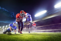 Giocatori di football americano nell'azione sulla grande arena immagine stock libera da diritti