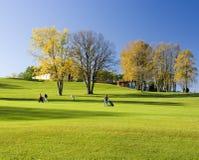 Giocatori di golf ambulanti in autunno Immagine Stock