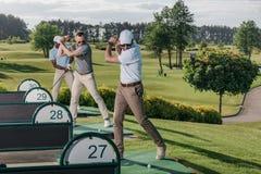 Giocatori di golf che giocano insieme golf al campo da golf Fotografia Stock