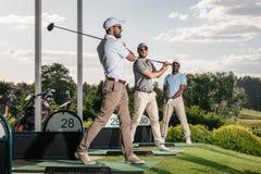 Giocatori di golf che giocano insieme golf al campo da golf Fotografia Stock Libera da Diritti