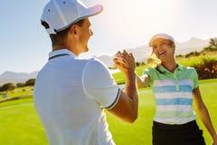 Giocatori di golf che stringono le mani al campo da golf immagine stock