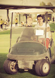 Giocatori di golf della donna e dell'uomo che guidano il carretto di golf Immagine Stock