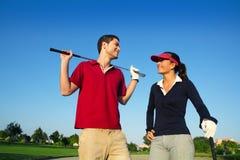 Giocatori felici delle coppie di terreno da golf giovani Immagine Stock