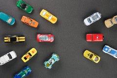 Giocattoli automobilistici variopinti L'appartamento stava trovando, su un fondo grigio Fotografia Stock