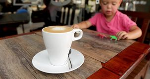 Giocattoli dei giochi da bambini accanto al cappuccino della tazza video d archivio
