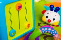Giocattoli del bambino che mettono su un materasso Fotografia Stock