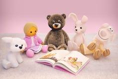Giocattoli del bambino e libro interessante situati sul tappeto Fotografie Stock Libere da Diritti